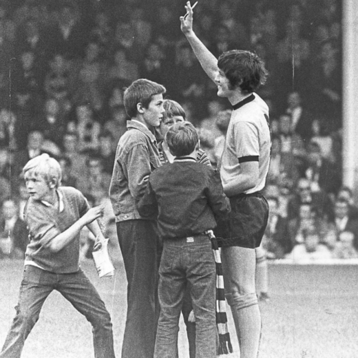 Footballer Peter Knowles surrounded by fans on the pitch