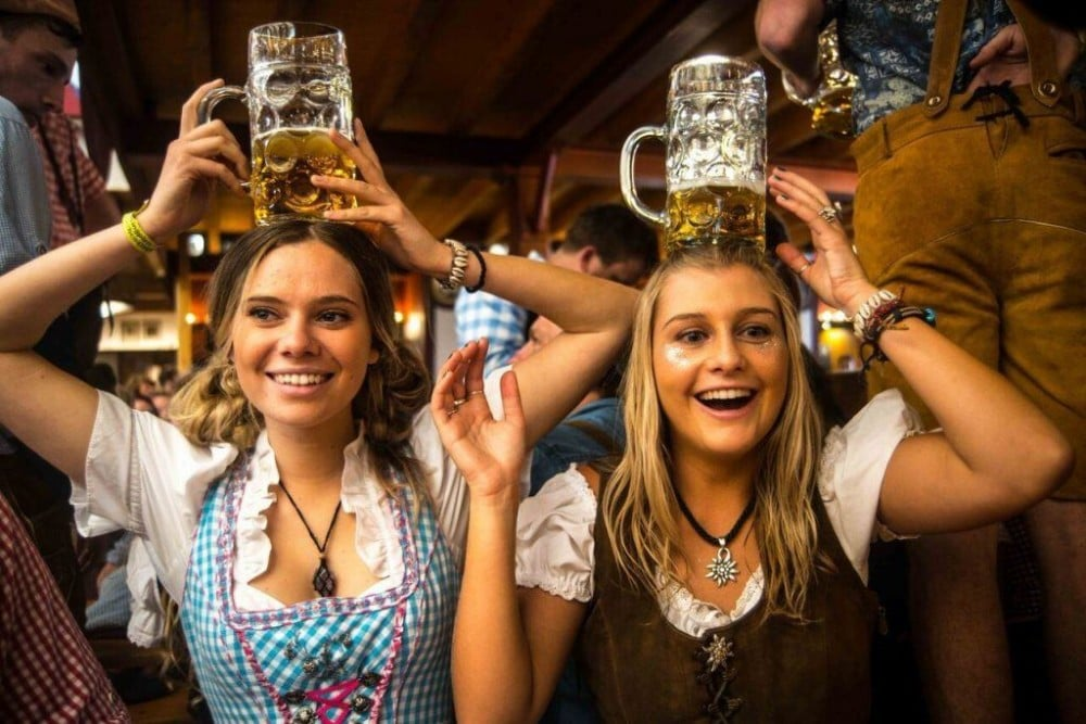 Two pretty blonge girs pose with beer steins on their heads