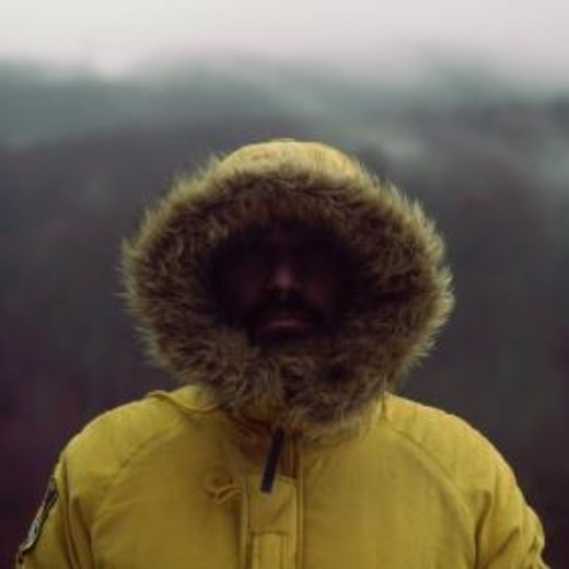 A man standing in the mountains with a fur hood covering his face