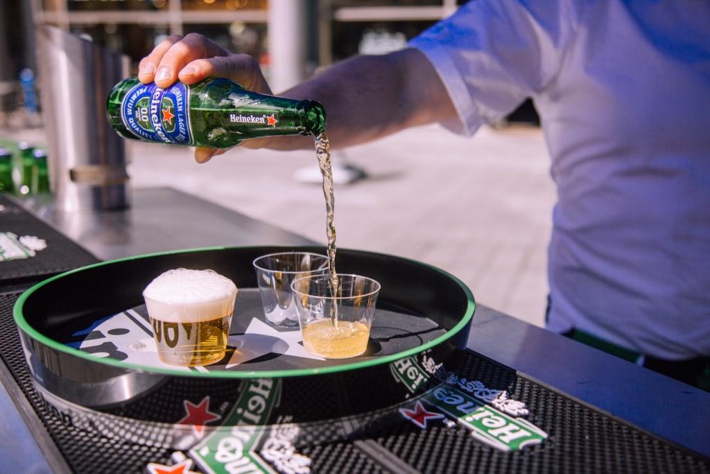 A man pouring a non alcoholic bottle of Heineken into a glass