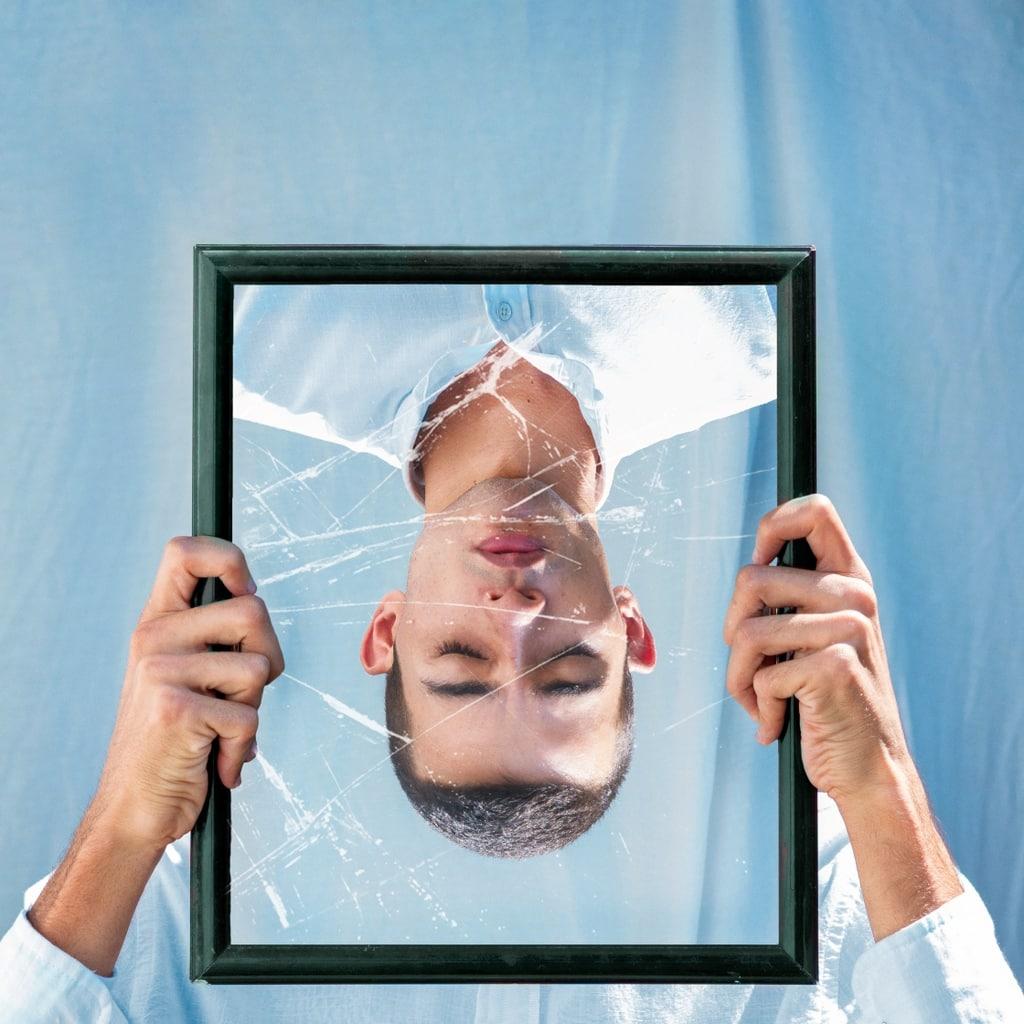 A man's reflection in a broken mirror