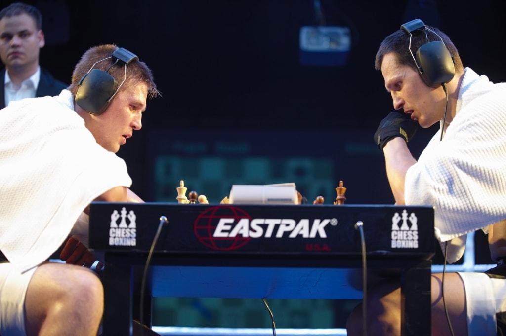 Two men in boxing kit playing chess