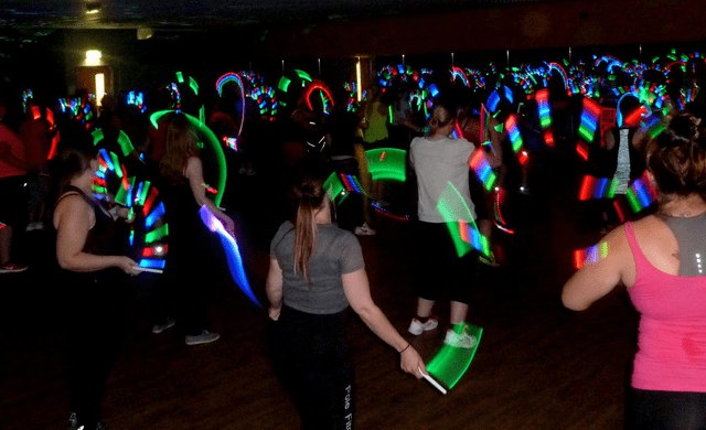 A group of women dancing with glow sticks