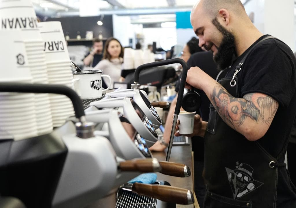 A barista adds milk to a coffee