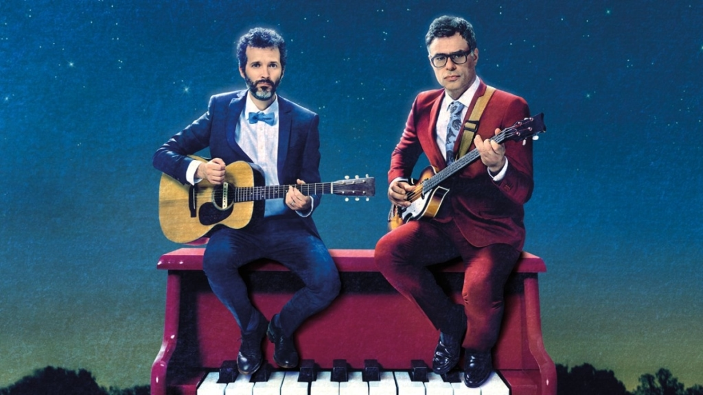 Flight of the Conchords, guitars in hand sat atop a piano