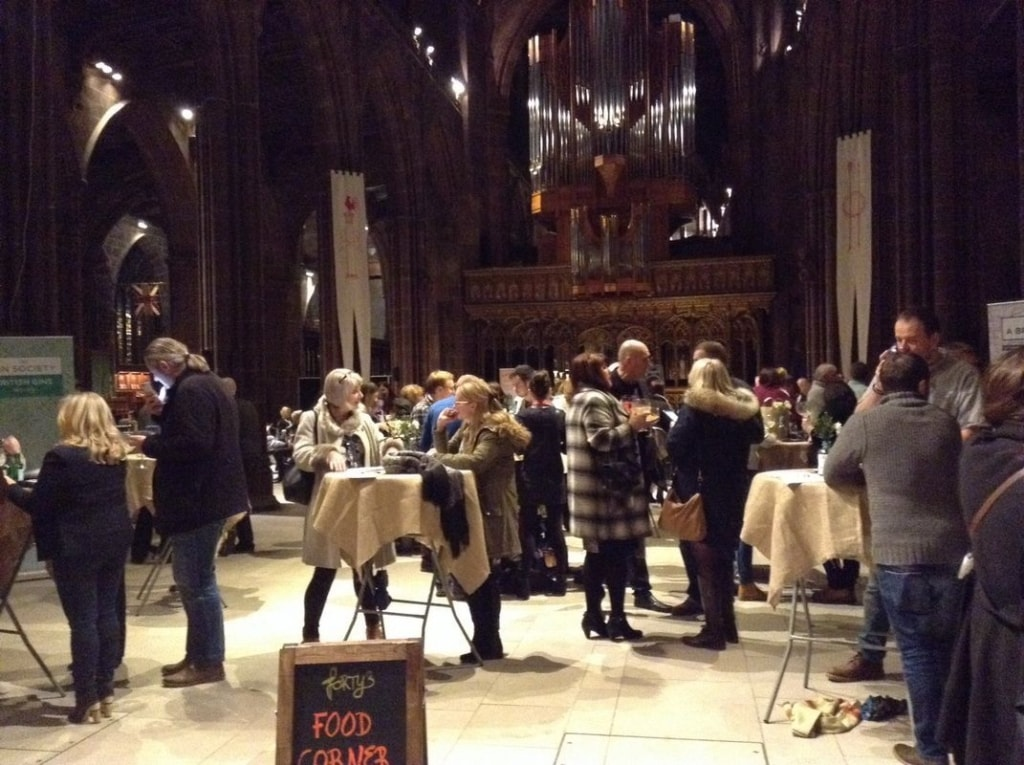 Groups of people enjoying drinks inside the Manchester Cathedral