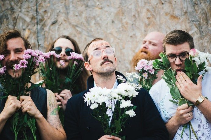 The Idles members holding bunches of flowers