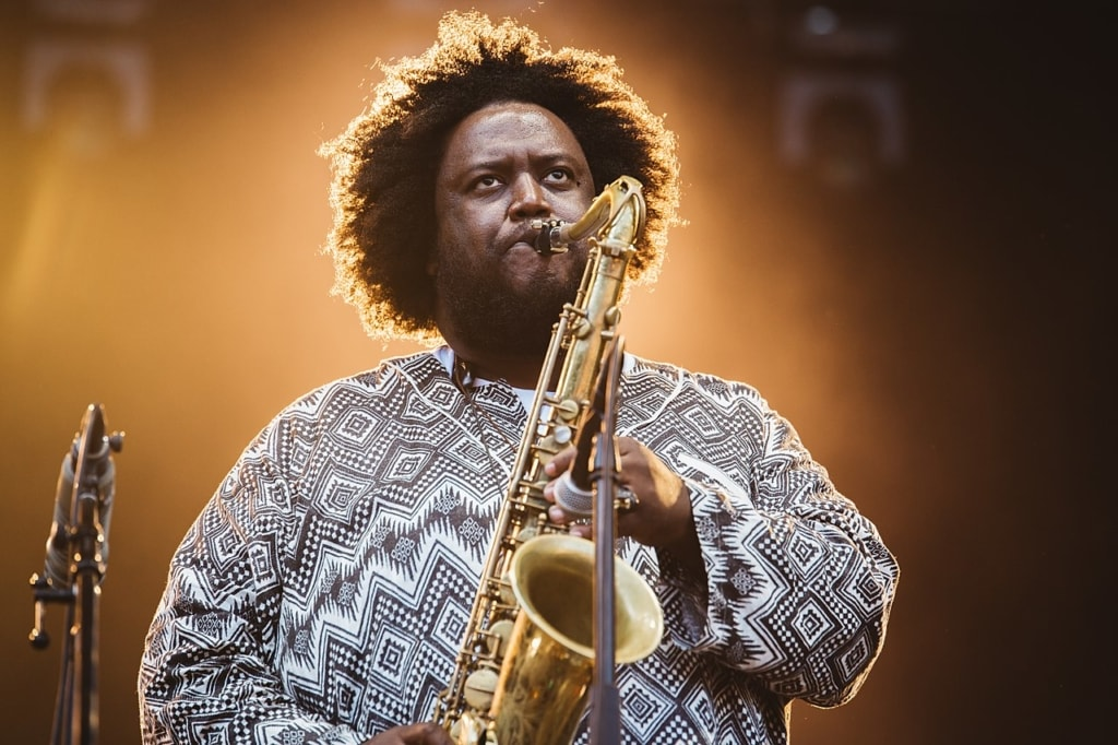 Kamasi Washington playing the saxophone onstage