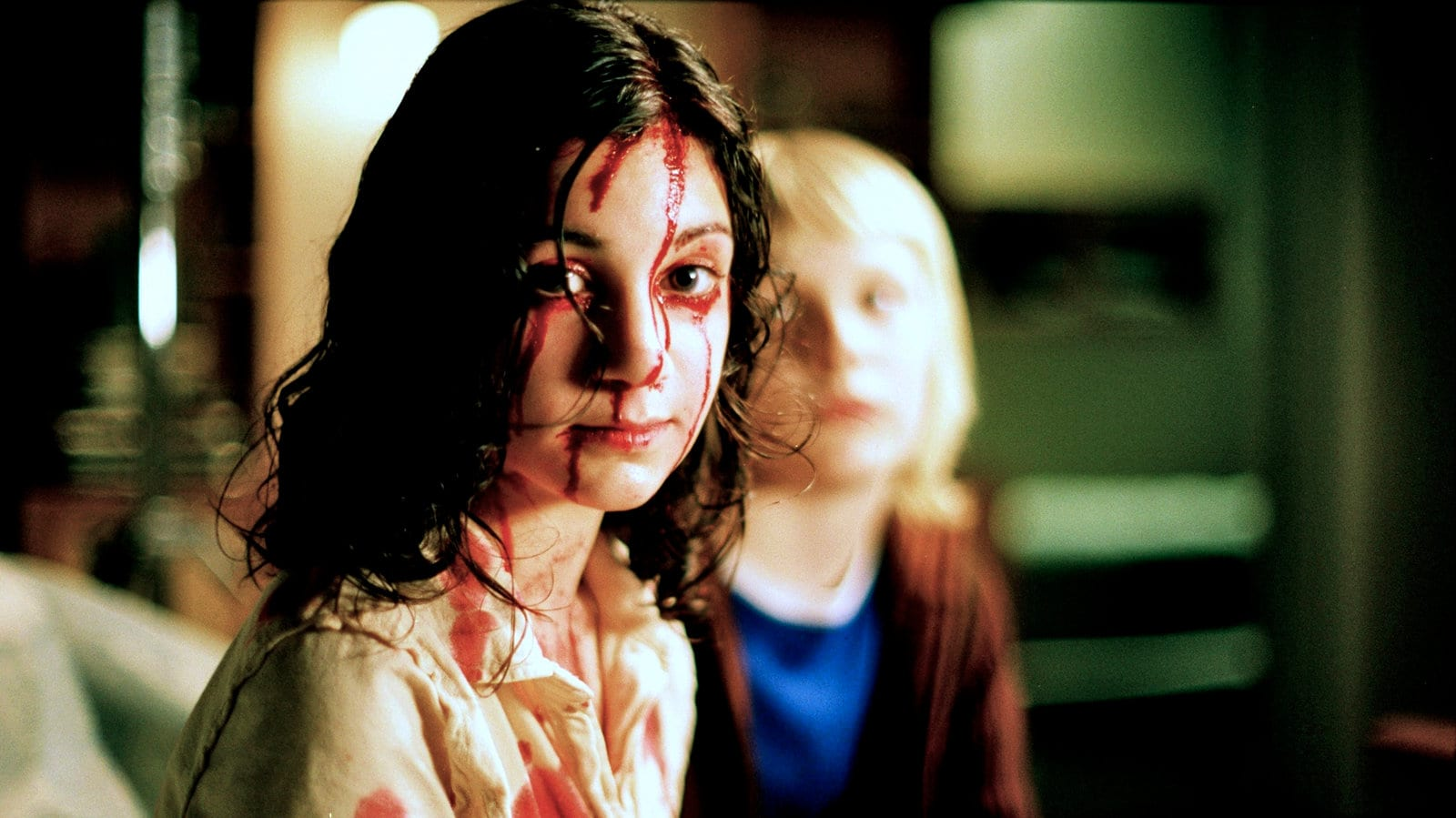 A still from Let the Right one in showing Eli with blood on her face and Oskar in the background