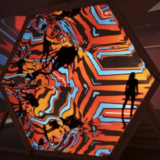 A woman looks through a giant kaleidoscope
