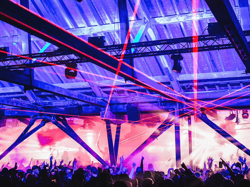 Party goers dance inside a large warehouse with strobe lighting