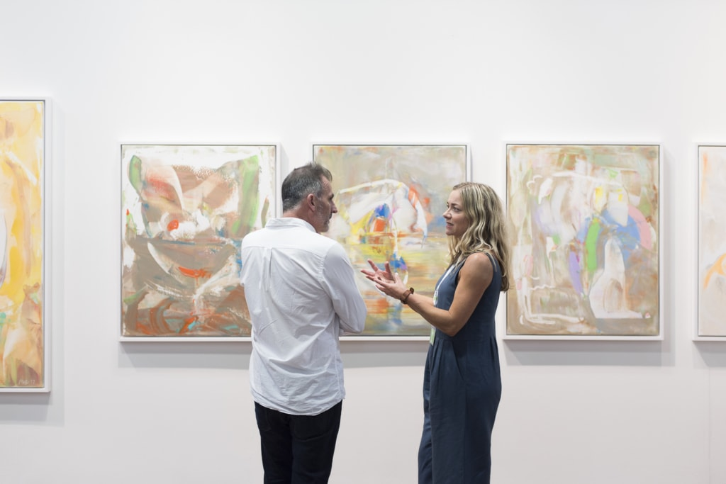 A man and woman discuss a piece of art work in a gallery