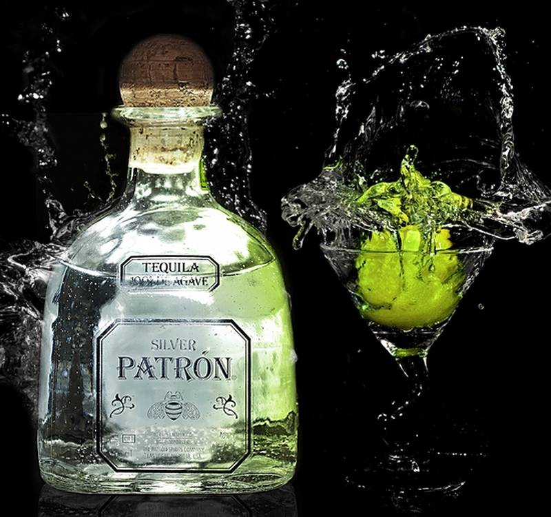 Bottle of silver Patron tequila next to a glass