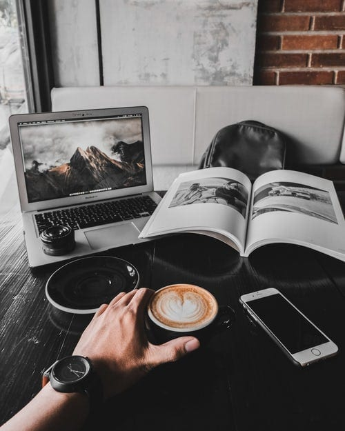 A coffee and laptop on a wooden table