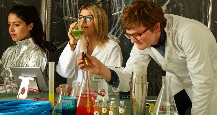 Three people in lab coats making a concoction