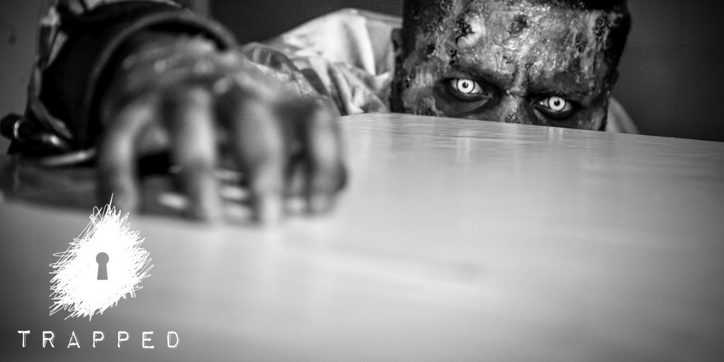 A zombie scratches hi hand across a table