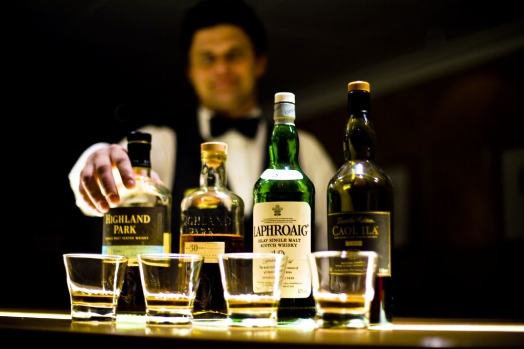 A bartender lines up Bottles of Whiskey on a bar