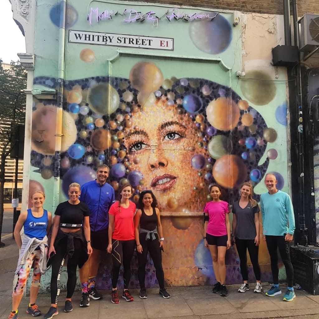 A group of street art tour runners pose outside street art on Whitby St, London